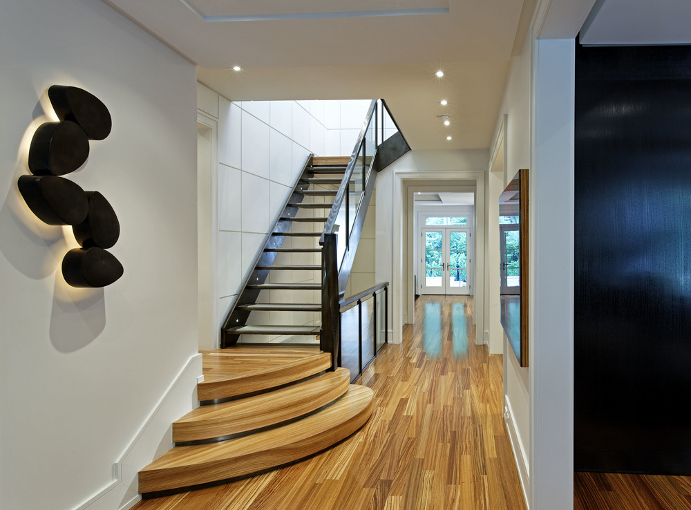 "At the core of this home is a central 3-storey circulation spine, combining angular and curved sculptural shapes, materials repetition and dramatic ""surprises"" to singular effect. Beyond the entry, the sconce curves are repeated in deep stair base steps; a grid pattern appears in the 2-storey wall panelling and in the floating rail of a light-filled stair way."