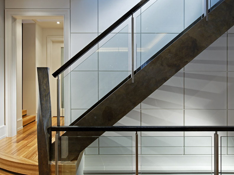 This clean, open and contemporary interior responds to this young family's modern tastes, but references the traditional exterior elements, grey-brown stone / black-brown trim, in elements such as the flooring material and stair's dark steel patina. The stair structure floats from and contrasts with the wall panels, floating glass panels float within its railing.