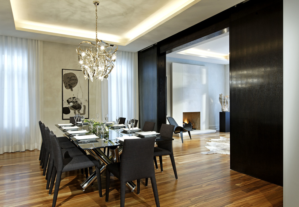 Within a traditionally styled house, a clean, open and contemporary interior responds to this young family's modern tastes. Both gracious entertaining and intimate family life are supported and enhanced by this modern but warm and timeless surrounding. The gathered sticks table base, twisted metal pendant and art finished walls animate this minimalist dining room, separated from the living room by double layered sliding doors, which simulate an unbroken wall when closed.