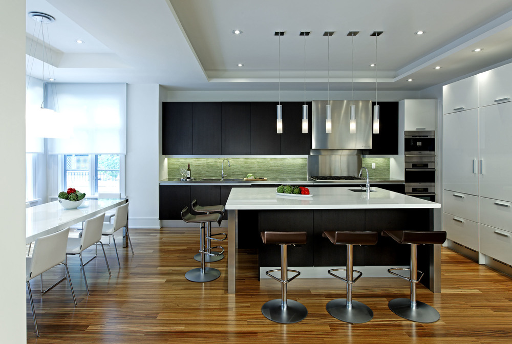 Within a traditionally styled house, a clean, open and contemporary interior responds to this young family's modern tastes. Both gracious entertaining and intimate family life are supported and enhanced by this modern but warm and timeless surrounding. In the generous, light-filled kitchen's asymmetrical layout, the sink, cook top and ovens align on a single dark wall; the storage / refrigeration on a white one. The whole family can gather at the large, square island.