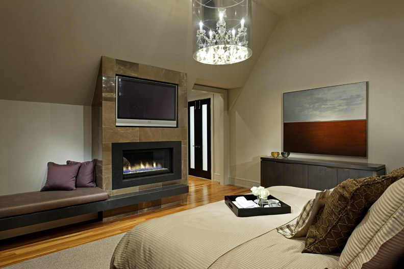 Within a traditionally styled house, a clean, open and contemporary interior responds to this young a family's modern tastes. Both gracious entertaining and intimate family life are supported and enhanced by this modern but warm and timeless surrounding. Deep tones add intimacy and richness to this bedroom, in which the fireplace, TV and fabric-wrapped bench form one functional, cohesive unit tucked below ceiling slope.
