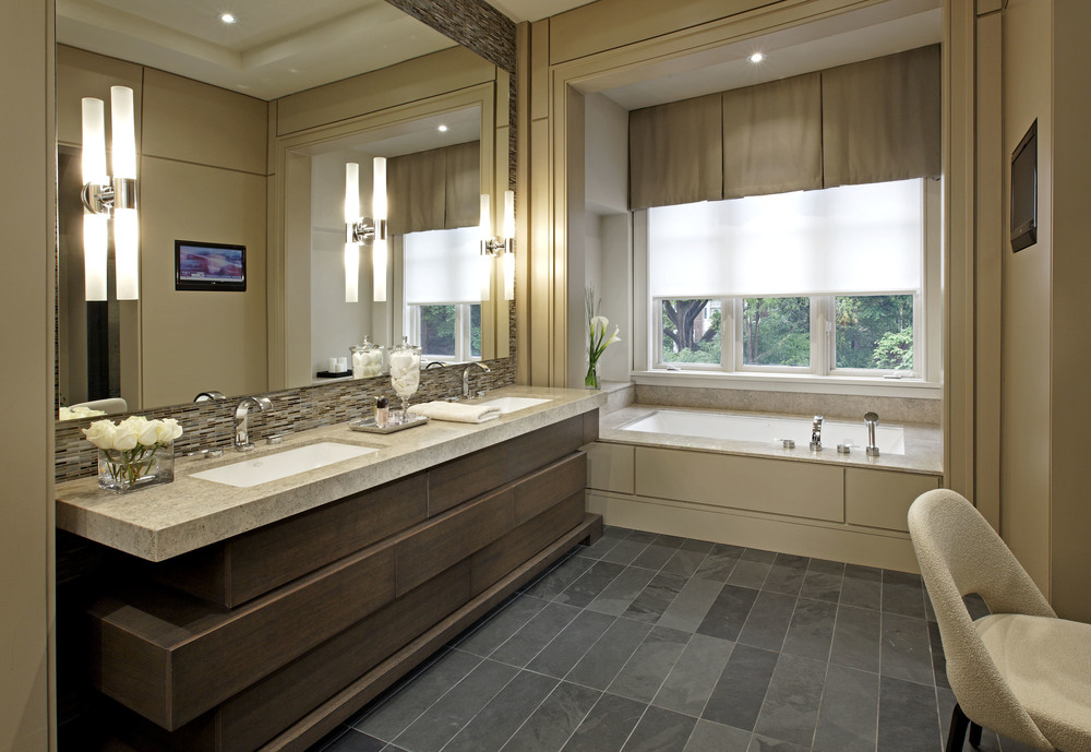 Within a traditionally styled house, a clean, open, contemporary interior responds to this young family's modern tastes. The serene master ensuite reflects those tastes, with its sophisticated milk chocolate palette and interesting textures. Custom fittings include the large double vanity with stacked and staggered drawers, make-up area and tub with a view.