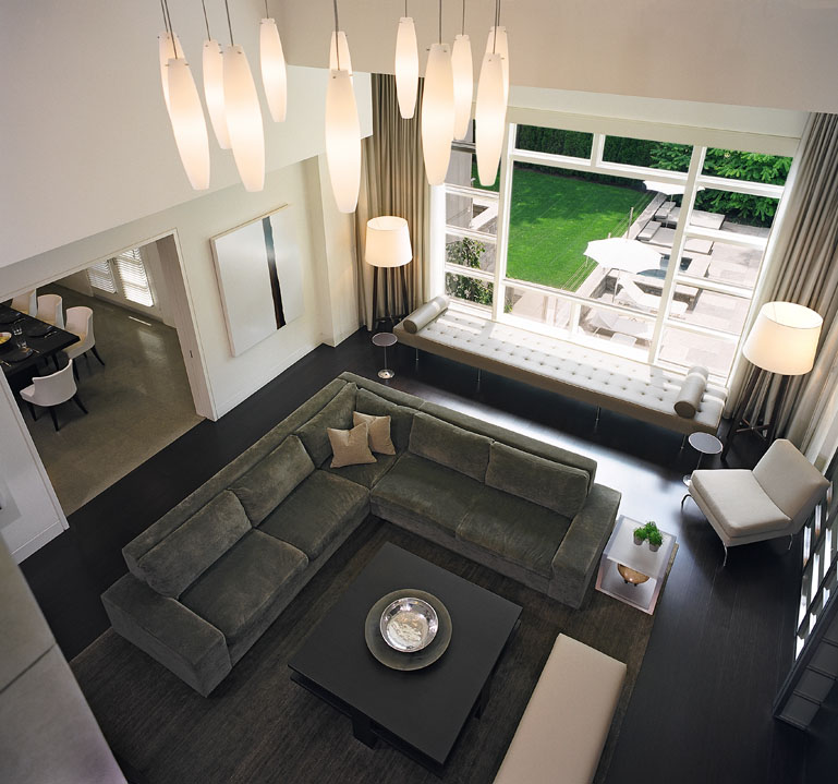 Designed to provide the perfect backdrop for a growing modern art collection, the orderly living room of this new 3-storey family home is simply furnished with both classic pieces and unique custom-designed items. Seen from above, the 2-storey great room features rich natural materials and finishes, accented with sleek glass and stainless steel details, all masterfully lit.