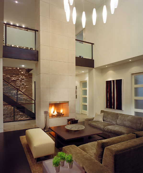 Designed to provide the perfect backdrop for a growing modern art collection, the orderly living room of this new family home is simply furnished with both classic pieces and unique custom-designed items. In its 2-storey great room, a stunning fireplace wall emphasizes the floating stair and 3-storey stone wall at the home's core. A custom light fills the open volume.