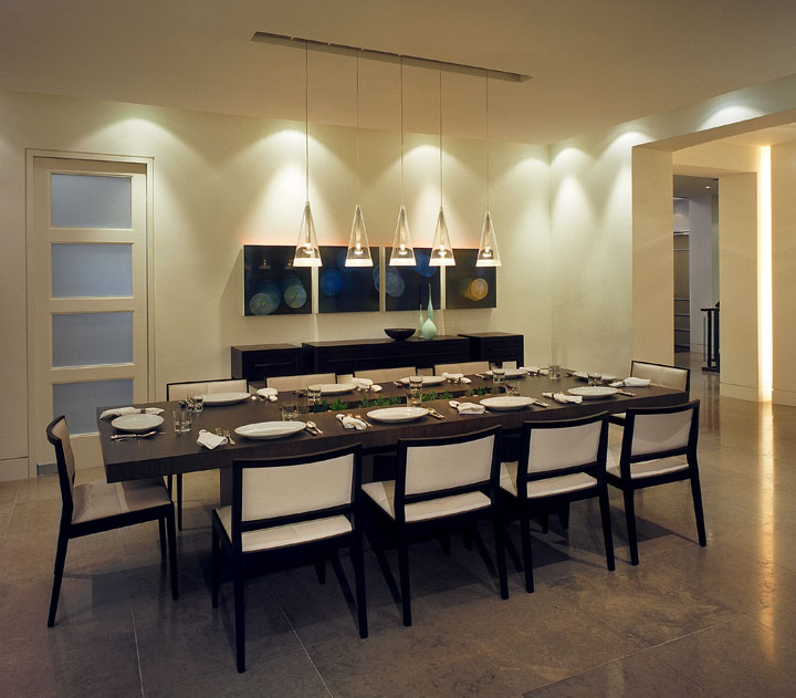 Designed to provide the perfect backdrop for a growing modern art collection, this new 3-storey family home is simply furnished with both classic pieces and unique custom-designed items. In the dining room, these are enhanced by layers of lighting, with pendants dropping from a ceiling slot reflected in the custom-designed table's centre recess, amplified by graceful perimeter cove lighting.