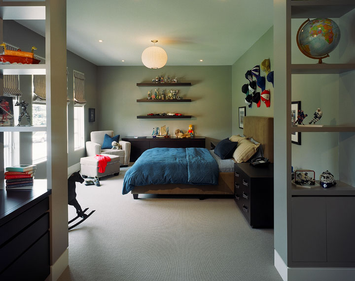A vestibule defining the homework area, closet and bath breaks up and adds intimacy to this large bedroom for a 10 year-old boy. Leather handles on custom chests, along with the corduroy bed upholstery and denim spread will work well long after the toy collection is replace by teenage interests.