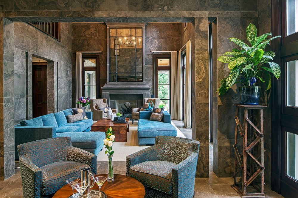 Skillful layering can be seen where the sitting room opens into the expansive great room. The local Eremosa stone tile walls establish remarkable warmth and richness and the smooth stone surfaces contrast with the lush, strié chenille upholstery and soft wool drapery treatments. The vertical piercing of the archway columns provides a striking counterpoint to the cadenced horizontal pattern of the wall panels.