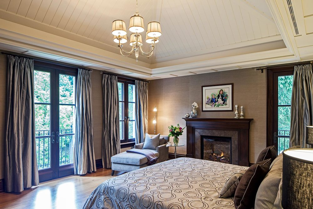 Cleverly integrating ventilation ducts, the painted wood panelled ceiling emphasizes the gracious expansiveness of this tranquil room. Extra-full pale silk drapery flanks the large mahogany framed windows overlooking the forest landscape. Mahogany also completes the St-Marc-des-Carrieres limestone in the custom fireplace surround. The walls are covered in pale grey grass cloth.