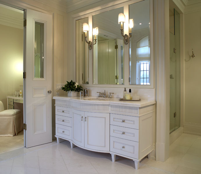 This client wanted his new home to celebrate his North American achievements and European heritage. After conceiving all the interior volumes and spaces, we used a variety of motifs, textures and patterns so that each room has its own mood, yet a common richness unites the home. In the centrepiece of her bath, the vanity's graceful curves and fine detailing add classical yet feminine character.