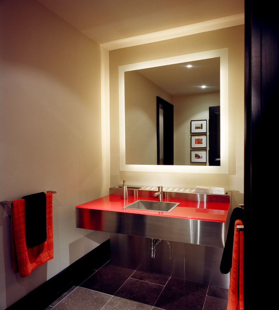 Filled with bright colour and reflective surfaces, the guest bath in the bar area of this home reflects the entertainment area. The sleek, wall-hung, stainless steel vanity was custom-designed for the space and features a red glass counter top with integrated towelette dispenser and waste container.