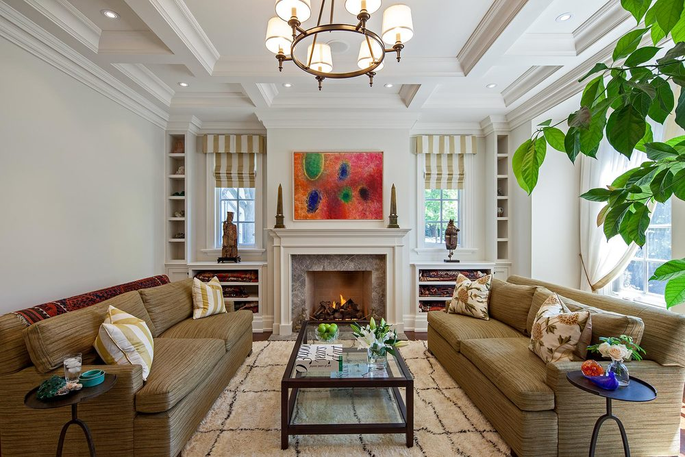 "Perfectly symmetrical, the complex wall and ceiling details are both elegant and functional. The marble fireplace centres a carefully planned storage wall that flanks the windows with small niches housing gemstone specimens collected by the owners, both geologists. The painting is ""Celestial Gathering"" by historical Canadian artist Michael Forster. Below a historic sculpture and mask, large shelves provide storage for several antique carpets. The coffee table and seating were existing; new upholstery stands up to use by children and pets, as does the handmade Jan Kath carpet. The crewel work cushion covers reflect the owner's love of textiles."