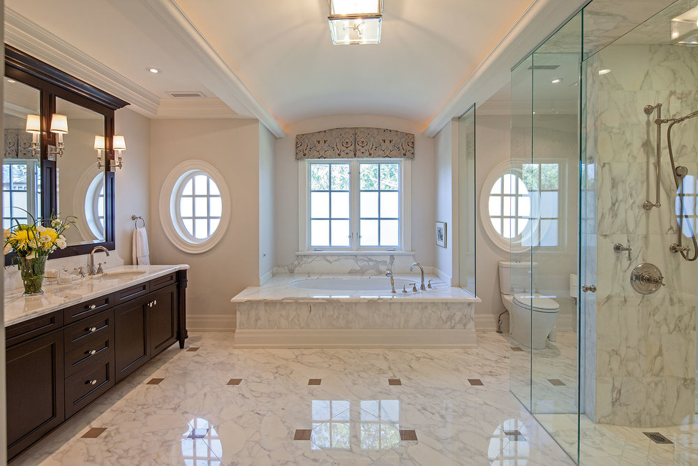 The barrel vaulted ceiling with recessed lighting reinforces the symmetry of this generous and elegant space. A coffered ceiling delineates the vanity area; opposite, the remarkably cleanly detailed glass partitions define the curbless shower and toilet areas. For privacy, the windows are coated with an easy-to-maintain translucent frosted film. Over the bath, a printed silk window valance extends to the ceiling, emphasizing its curve.