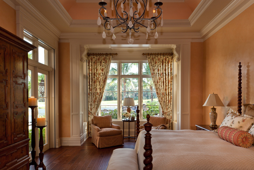 In the Florida sunshine, peach-toned Venetian plaster glows against the hickory flooring and complex millwork details that establish the character of this elegant master bedroom.