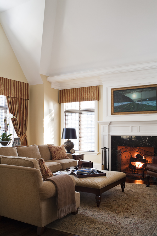 We worked with the builder of this very traditional home to resolve and sculpt the shape of this 1 ½ storey room under the sloping roof lines, creating a light, open space that we warmed with a palette of deep reds, golds and tans. The family finds it the perfect spot to curl up and watch a movie after dinner. The drapery valance conceals the housing for the wooden Venetian blinds used to darken the room for that purpose.