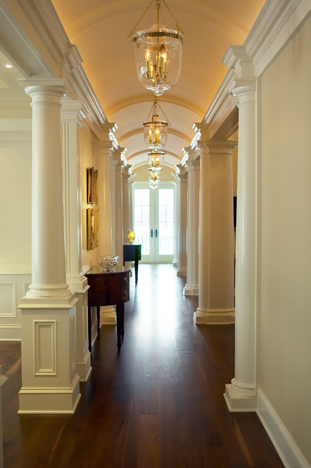 "We designed this classic, spacious and comfortable ""farmhouse"", situated on rolling acres of farm and woodland in Upper New York State, to serve the family for years to come. Columns, archways and a series of elegant lanterns create a serene rhythm in the wide central hall."