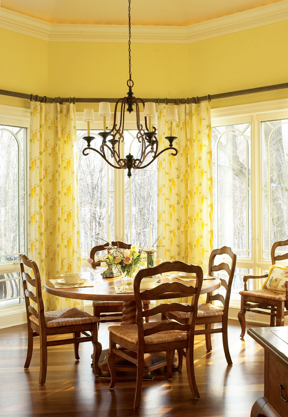 In the family farmhouse kitchen, a large bay window floods the room with light and provides a woodland view. We used a sunny yellow palette and cheerful semi-sheer draperies to welcome and amplify the breakfast sunlight.