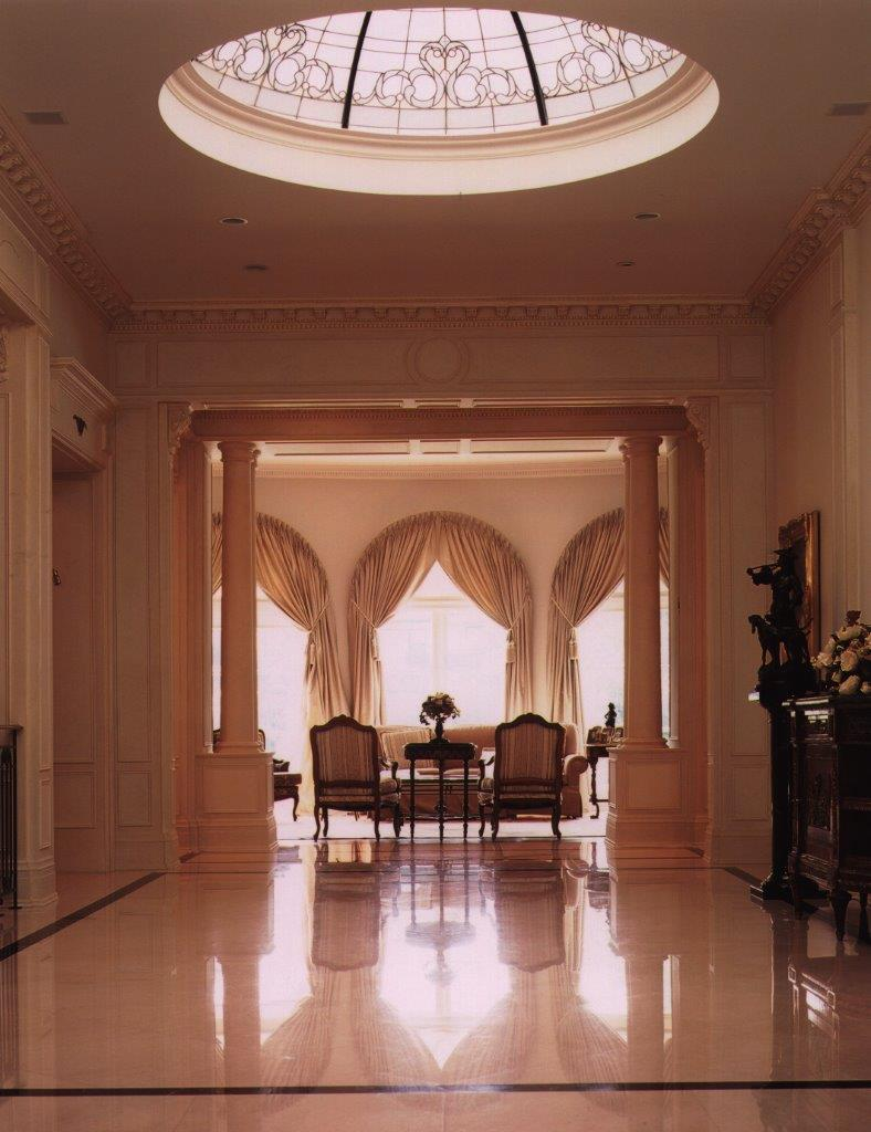 This sophisticated and sociable couple commissioned a grand traditional home to suit their busy family and entertainment lifestyle. With its exquisitely detailed columns, mouldings and cornices, gleaming crema marfil slab flooring bordered by green marble and subtle aged rubbed art wall finish, the grand reception hall is the focal point for the interior. We designed a custom-fabricated leaded glass convex lens to finish the skylight and create a brilliant conservatory effect.