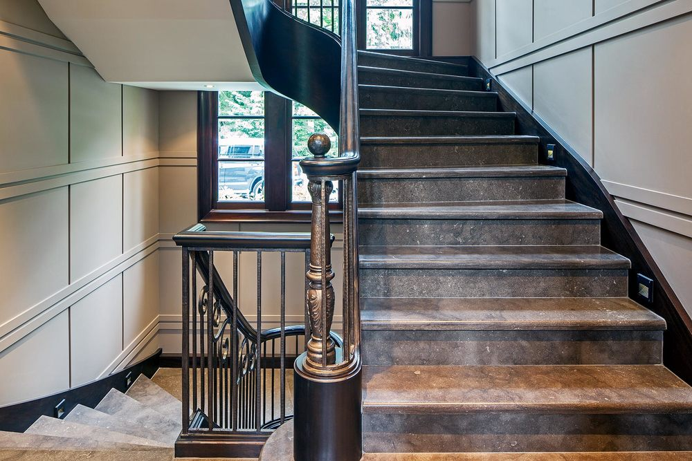 Texture is a key design element in this stately home, as seen in the double-rail-and-reveal detail of the contemporary painted wooden wall panelling, the wooden cladding on the steel stair structure into which stone steps have been set and the contemporary bronzed iron railing.