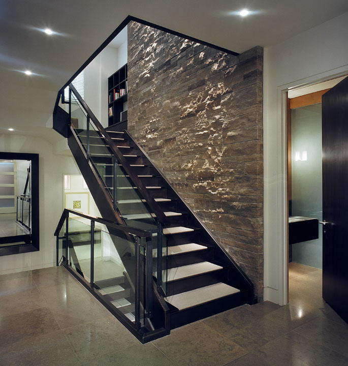 We developed important details early so the builder could incorporate the necessary supporting requirements, such as the huge light-washed stone wall at the core. The sleek metal and glass stair floats two inches away from it in striking contrast with its rough texture, washed by high-intensity spotlights concealed in a second floor ceiling slot.