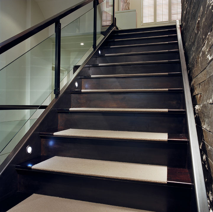 The central steel stair floats against the stone wall, connecting seamlessly with wood landings on one continuous stringer, which incorporates LED lighting. The finely detailed glass and steel railing creates a visual lightness to the massive, yet elegant, structure.