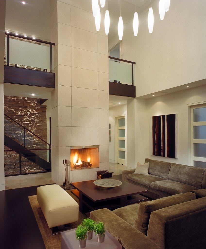 In its 2-storey great room, a stunning fireplace wall emphasizes the floating stair and 3-storey stone wall at the home's core. A custom light fills the open volume.