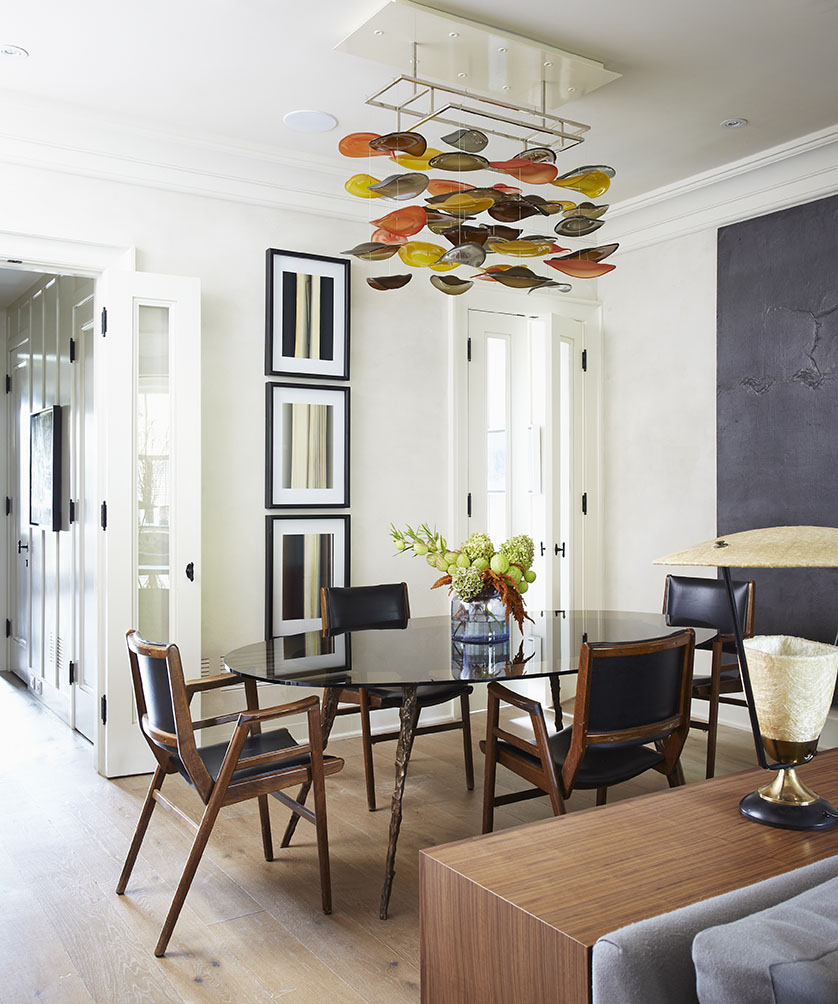 Originally 5 feet deeper, this dining room was awkwardly capacious and square. Creating a more functional layout, the 5 feet was taken to create a butler's pantry, closet and powder room, which are normally rare features for homes in the surrounding historic neighbourhood.   Carrying through the home's eclectic mix of old and new, 1940's office chairs provide restful seating around a custom designed smoked glass dining table with molten bronze legs. A unique, custom light fixture from Jeff Goodman Studio provides a soft glow, while reclaimed European oak flooring adds warmth to the room.
