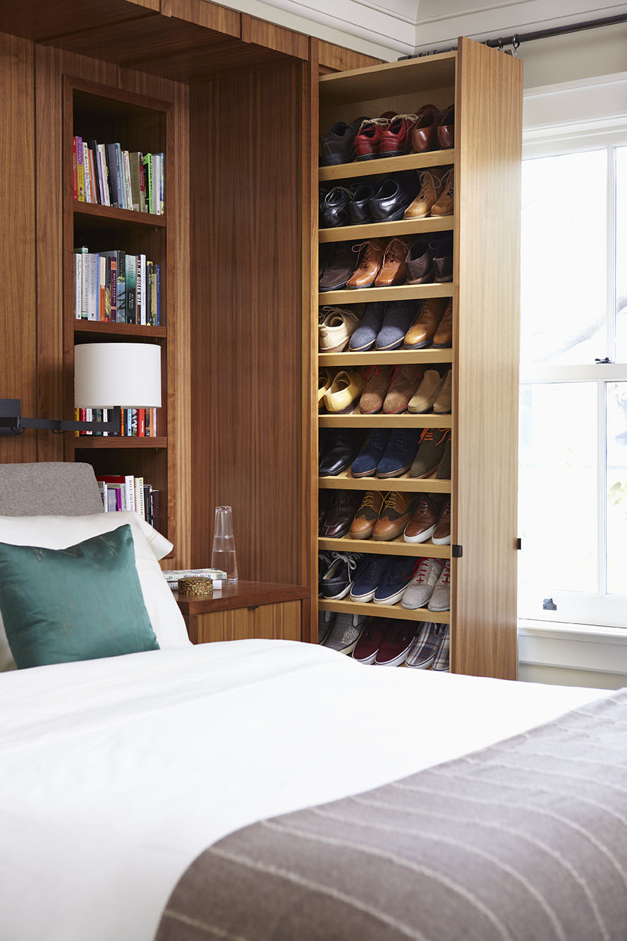 In this old Victorian rowhouse, it was important to create functional storage space wherever possible. Concealed behind walnut panelling, and leaving a pocket for the adjacent drapery, a pull-out vertical closet houses 42 pairs of shoes.