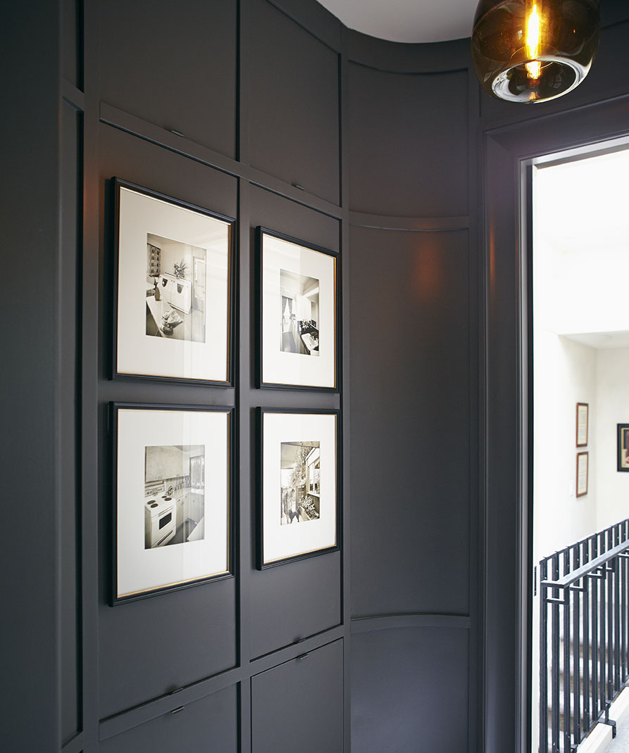 Leading into the master bedroom, this ante room was painted a dark, rich colour to diffuse the glow from a neighbouring skylight. Paneling conceals clothing storage and hampers.