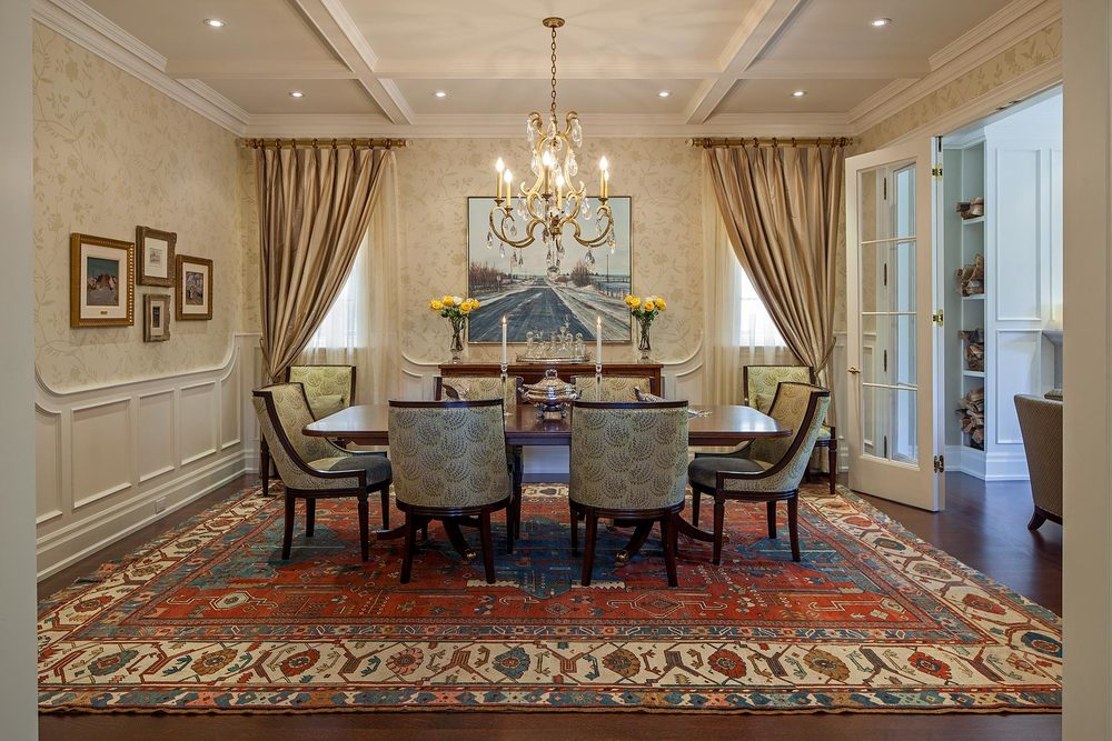 "This couple are avid collectors of antique carpets, fabrics and furnishing, and of course Canadian art as perfectly combined in this gracious dining room. Bounded by carefully thought out wall panelling and coffered ceiling details, their existing chairs surround a newly acquired fine mahogany pedestal table with matching server under a specialty handcrafted gold leaf and crystal chandelier. A fine c.1880 Bakshaish Persian carpet grounds the setting, while the silk drapery and floral overprinted grass cloth wall covering were chosen for their combination of lushness and simplicity. The large painting, ""Winter Road"" is by noted Canadian Western artist John McKee."