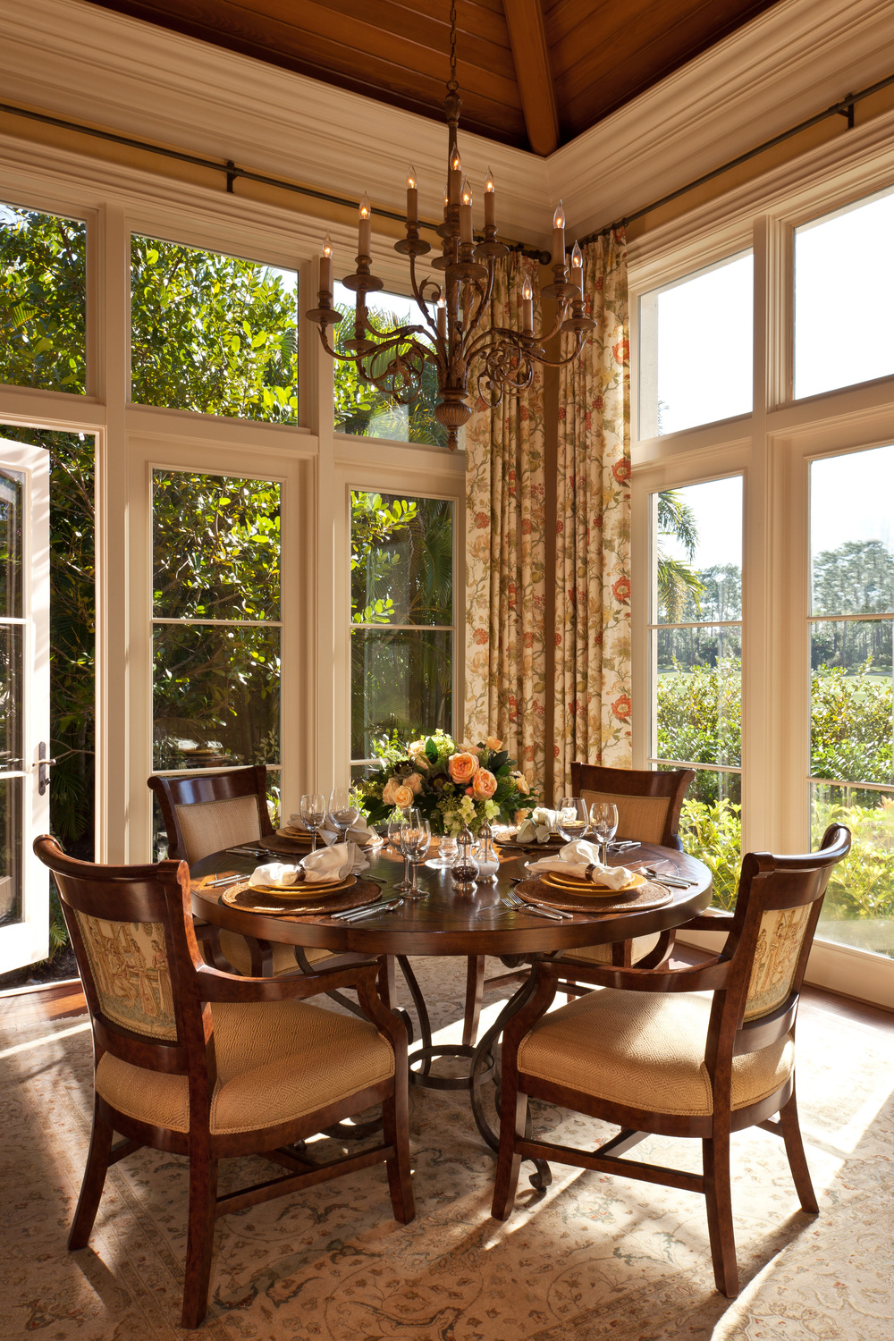 Below the carefully planned beamed cypress wood ceiling and surrounded by hurricane proof windows, this charming breakfast room is filled with Florida sunshine.