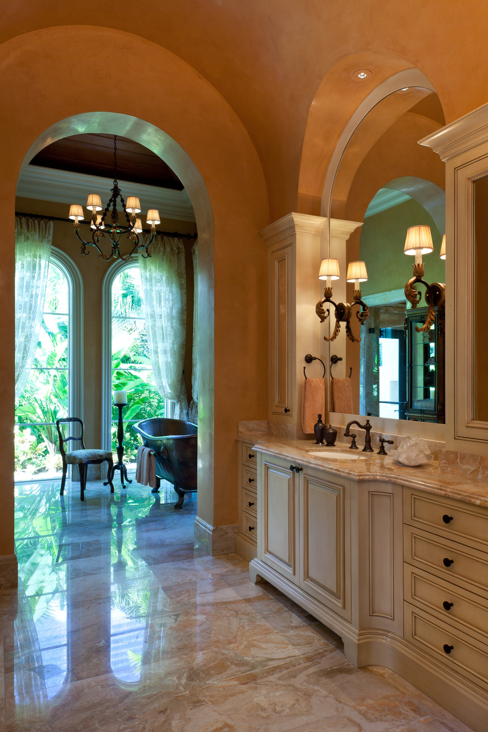 As in the other rooms in this exquisite Florida home, the architectural and cabinetry details were painstakingly developed to contribute to the interior design character individually and to work together beautifully. Here, the circles of the vanity mirrors reference the barrel vaulting of the ceiling and all the cabinetry was designed to enhance the volume. Venetian plaster, painted millwork and bronze fittings work well with the magnificent breccias oniciata marble slab flooring.