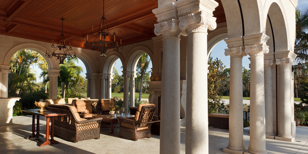 In the welcoming lanai of this Florida home, the columns and ceiling are typical of the extensive design detailing. Here, narrow slots between the double columns conceal remote controlled widow screens.