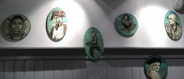 Paintings by Jon Langford, a reflection of the six artists who anchor the playlist at Chesapeake & Maine.