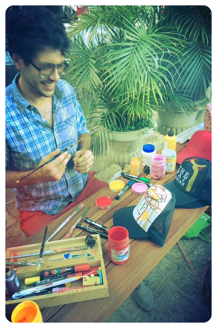 Street artist Smael customizing The Fat Radish caps for the Gastromotiva auction.