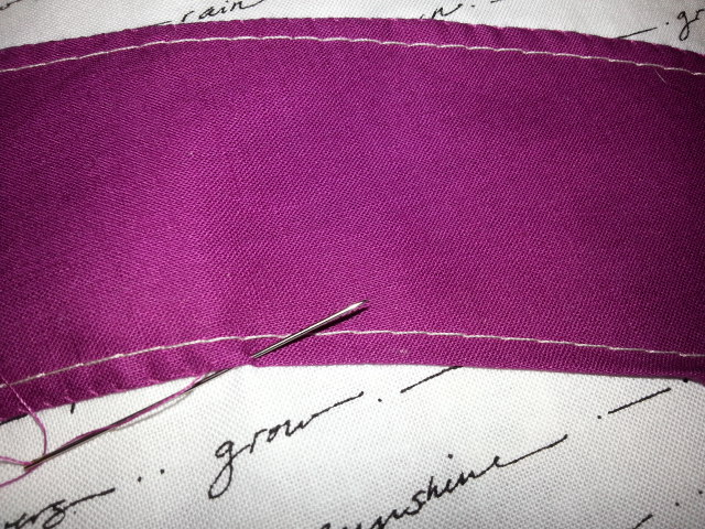 Detail of appliqué: White thread is the machine basting, the raw edge is turned under and the edge is being slip stitches