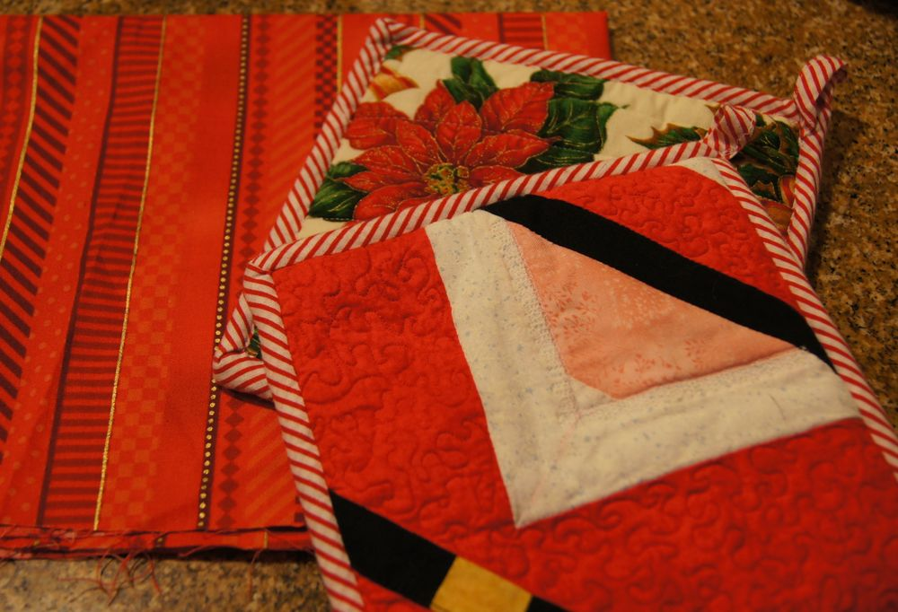Quilted Santas on one side of the potholders, poinsettias on the flip side.  Quilter--PBQ Guild member, identity unknown