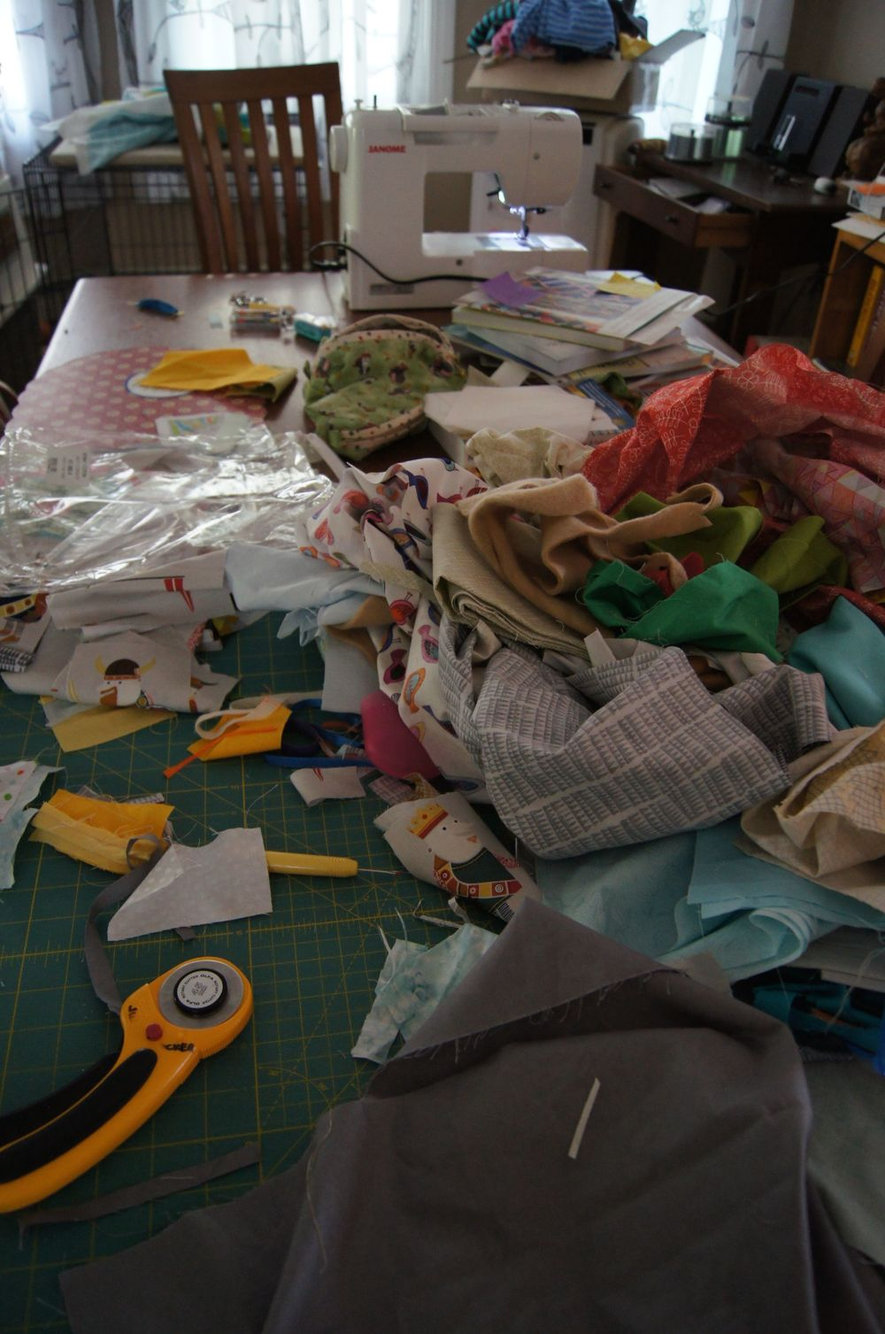 Creative cutting mess on my dining room table. It looks like a mess but the fabrics are organized by color and/or location in a section in the quilt.  The fussy cut pieces are in a separate stack.