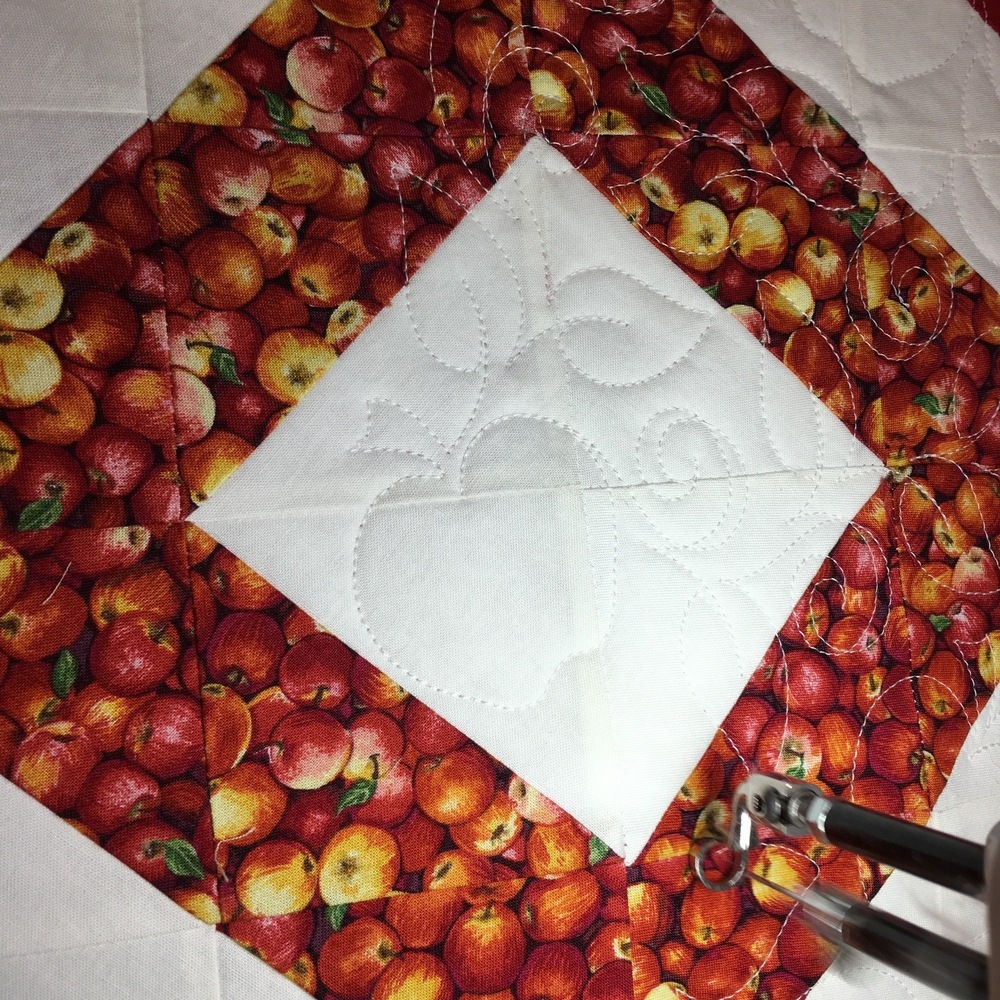 Detail of the longarm computerized apple quilting design