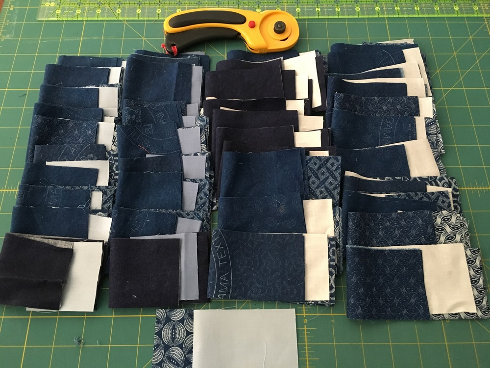 Indigo blocks ready for assembly and the quilt's label in front.