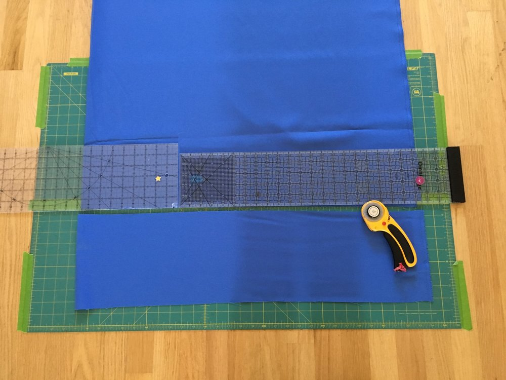 Cutting mat taped to the floor with rulers and rotary blade