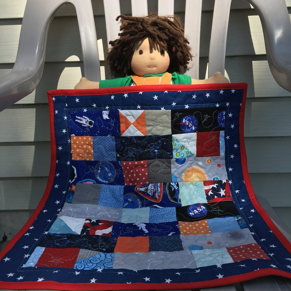 Micah, a  Bamboletta  Cuddle Doll, with the Space Doll Quilt, 16 x 19 inches