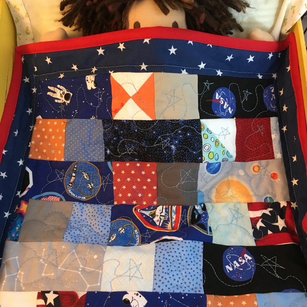 Micah suggling under the Space Doll Quilt