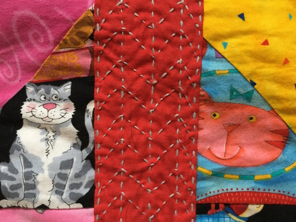 Close up of Visible Mending on a quilt. The cats seems to approve of the new addition!