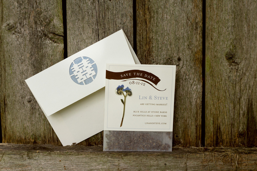 "Lin and Steve   Special Design Notes/Theme:   Asian-Rustic Charm; Forget-Me-Not seed packets were given out as save the dates; ""double happiness"" punched on the back of envelopes; envelopes lined in handmade blue paper;   real   forget me not flowers adhered to the outside of the seed pack label    Printing Method:   Digital press   Paper:  Strathmore natural white  ""These look amazing! I'm so happy with how they turned out!"" –Lin and Steve, New York City"