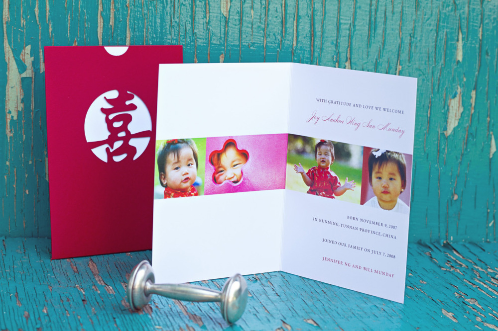 Joy   Special Design Notes /Theme:  We created a custom laser cut pocket envelope for Baby Joy. Her name was laser cut onto the front of the pocket in Chinese. A folded card was inserted into the pocket.  Printing Method:  Digital press  Paper:  100# coverstock; laser pocket in Carnival Red (other paper/color options available upon special order)