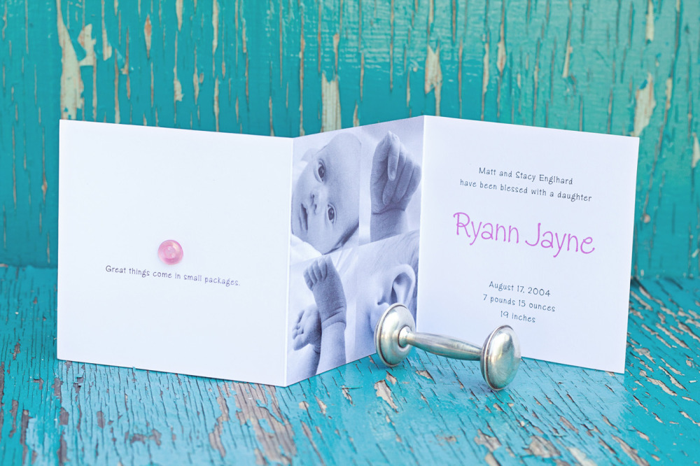 "Ryann Jayne   Special Design Notes /Theme:  Design incorporates up to 4 photos of your baby with a hand applied button in pink or blue on the cover; announcement folds down to a  5"" square  Printing Method:  Digital press  Paper:  80# coverstock"
