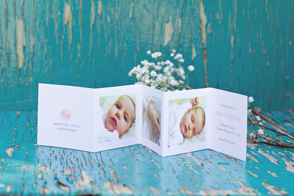"Svea   Special Design Notes /Theme:  Incorporates 3 photos of your baby with a hand applied button in pink or blue on the cover; announcement folds down to a  2 3/4"" square and placed into a glassine envelope. 3 1/2 x 5 mailing envelopes are included with your order  Printing Method:  Digital press  Paper:  80# coverstock"