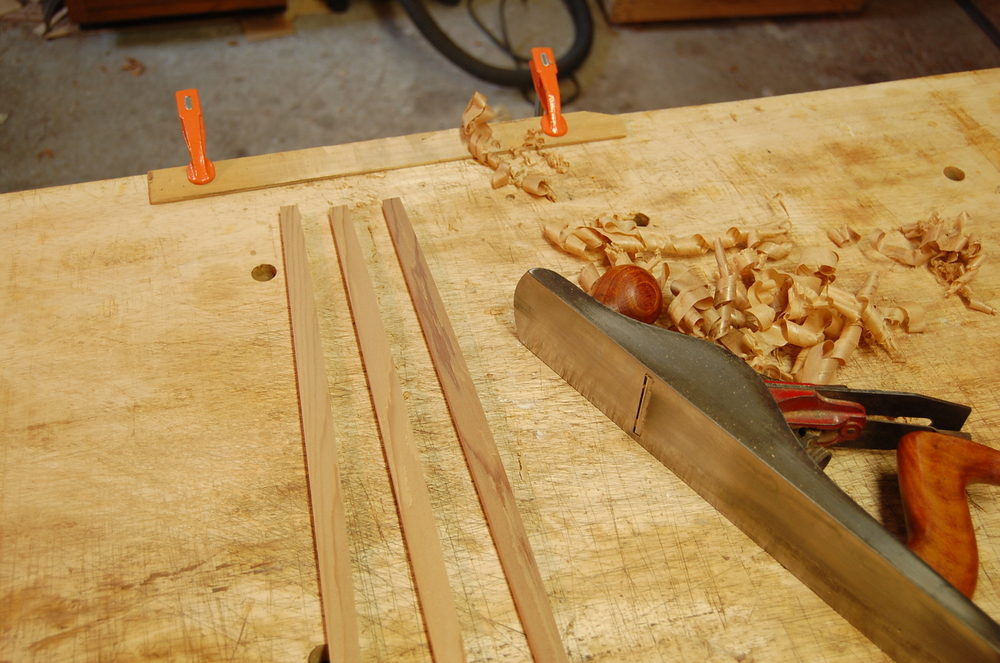 Planing down the back braces to 8 mm thick.  I'm using Western Red Cedar for its light weight.  The braces have already been curved in order to achieve a slight doming of the back.