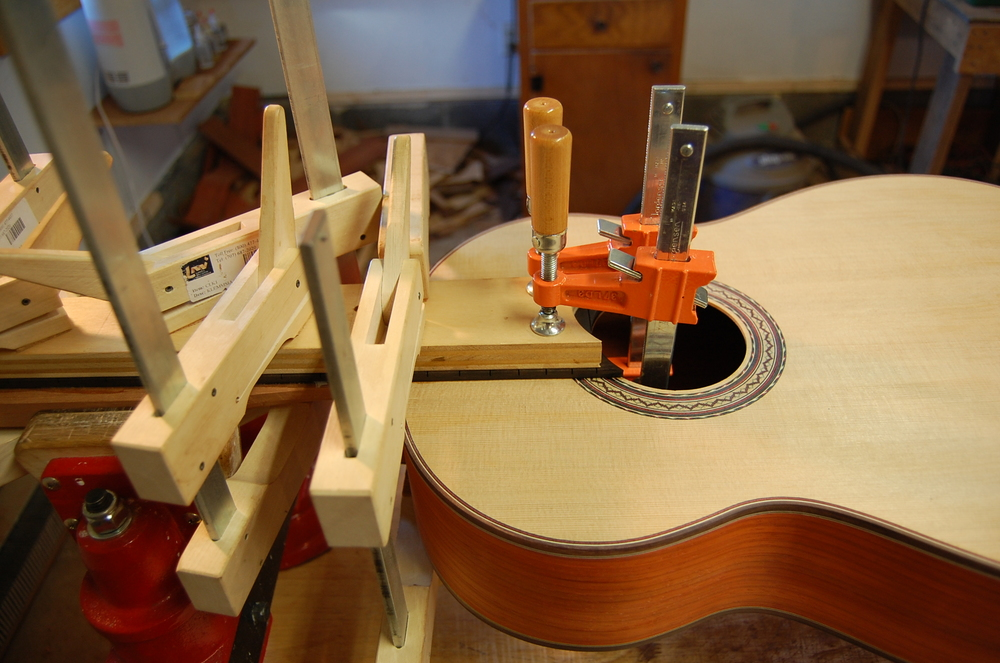 The gluing surfaces are sanded and prepared, and the fingerboard is glued on using high quality Epoxy.  Water-based glues have a tendency to cause some warping on a joint of this size.