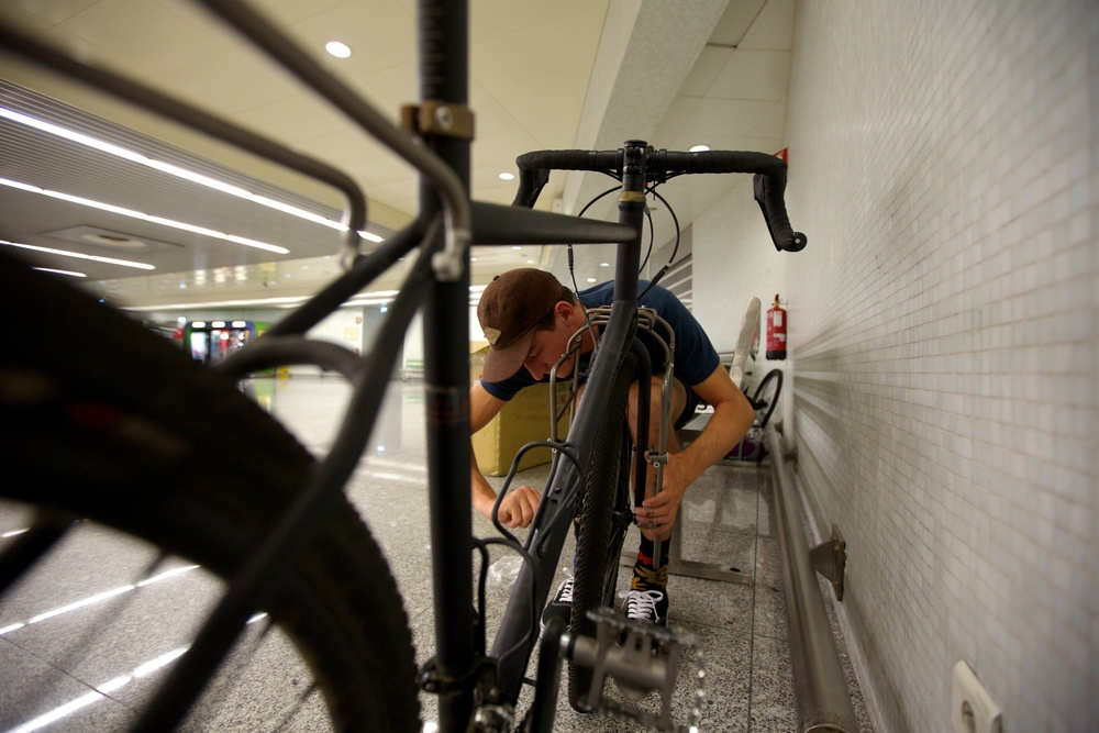 Keagan adjusts his front rack in the baggage claim of the Lisbon Airport, on Thursday afternoon, Itching to get outside and get those spokes salty.